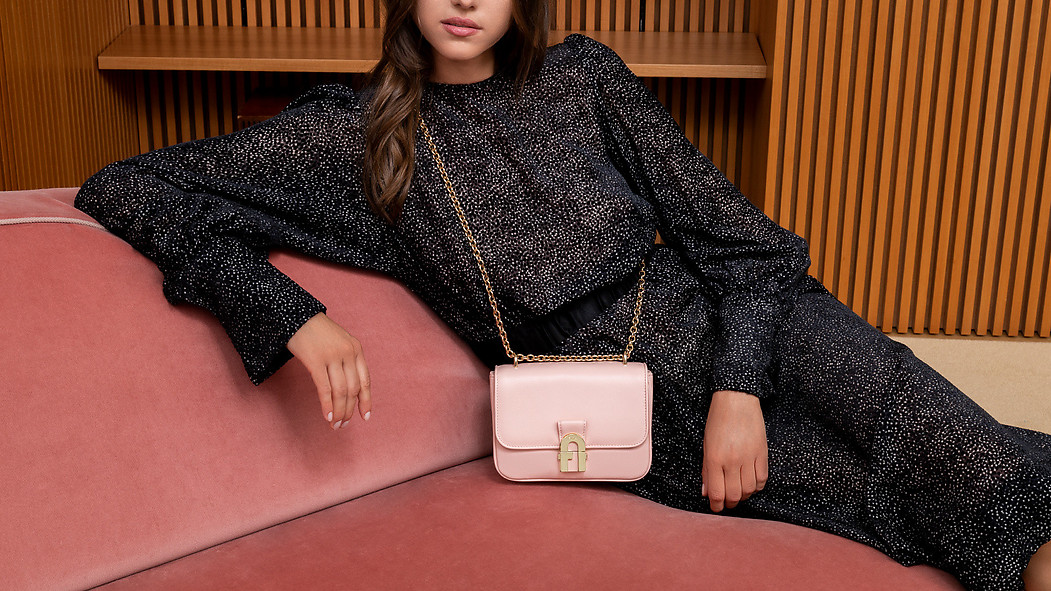 In a house in Milan, a female model is casually leaning on a pink couch, wodden shelves in the backgound. She wears a black dress and the pink Furla Cozy bag.