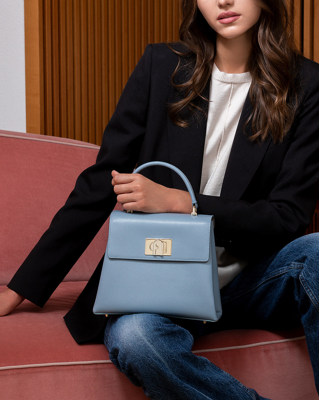 A white female wearing denim jeans, a white t-shirt and a black blazer holds a light blue Furla 1927 S Top Handle in her hand while sitting in a Milanese home environment.