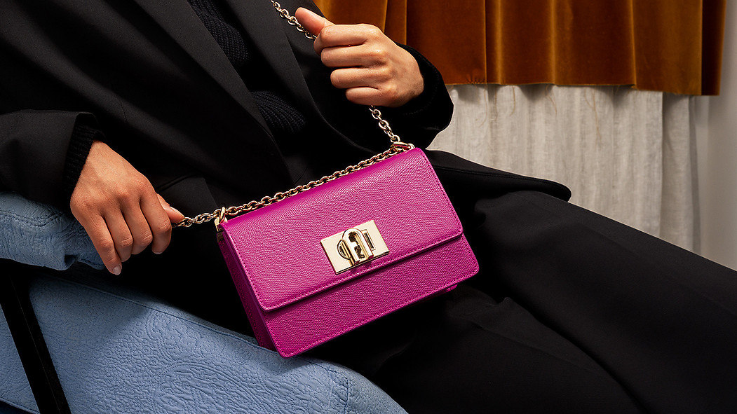 A white female wearing a black oversized dress holds a pink Furla 1927 Crossbody  while sitting in a Milanese home environment.
