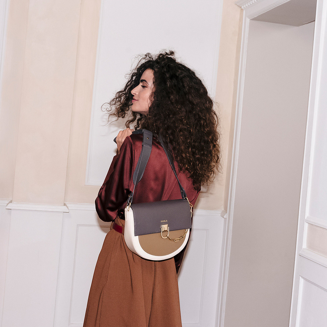 Chiara Scelsi is in her apartment, trying on bags. She is twisting and holding the new Furla Miss Mimi over her shoulder.