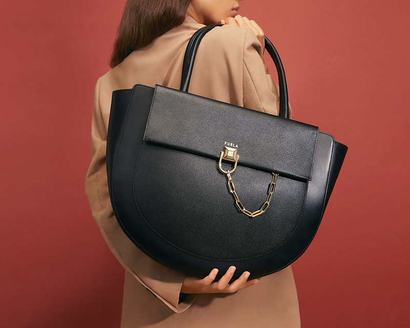 The back side of a model is captured while she holds the new Furla Miss Mimì maxi bag over her shoulder with one hand while the other hand is place beneath the bag. She is wearing a beige blazer and the background is red.