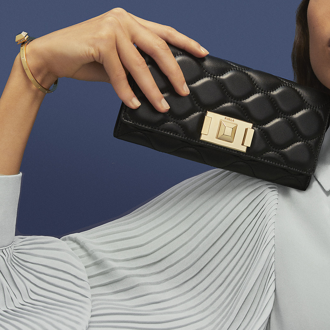 A white woman is holdin a black wallet over her sh...