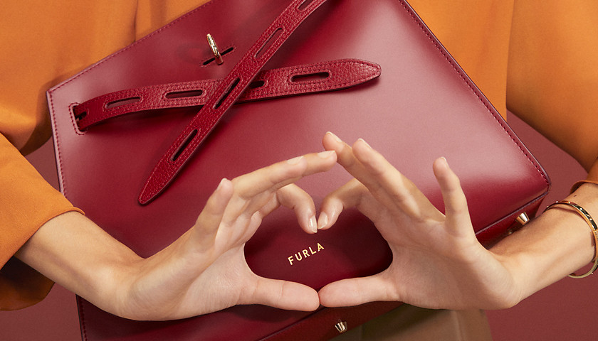 A Furla Margherita color ciliega is the focus of t...