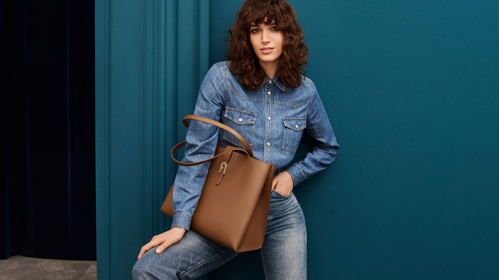 The model and actress Greta Ferro is staning in front of a blue wall. She is wearing a denin shirt with denim heans and holding the new Furla Sofia Tote bag on the knee.
