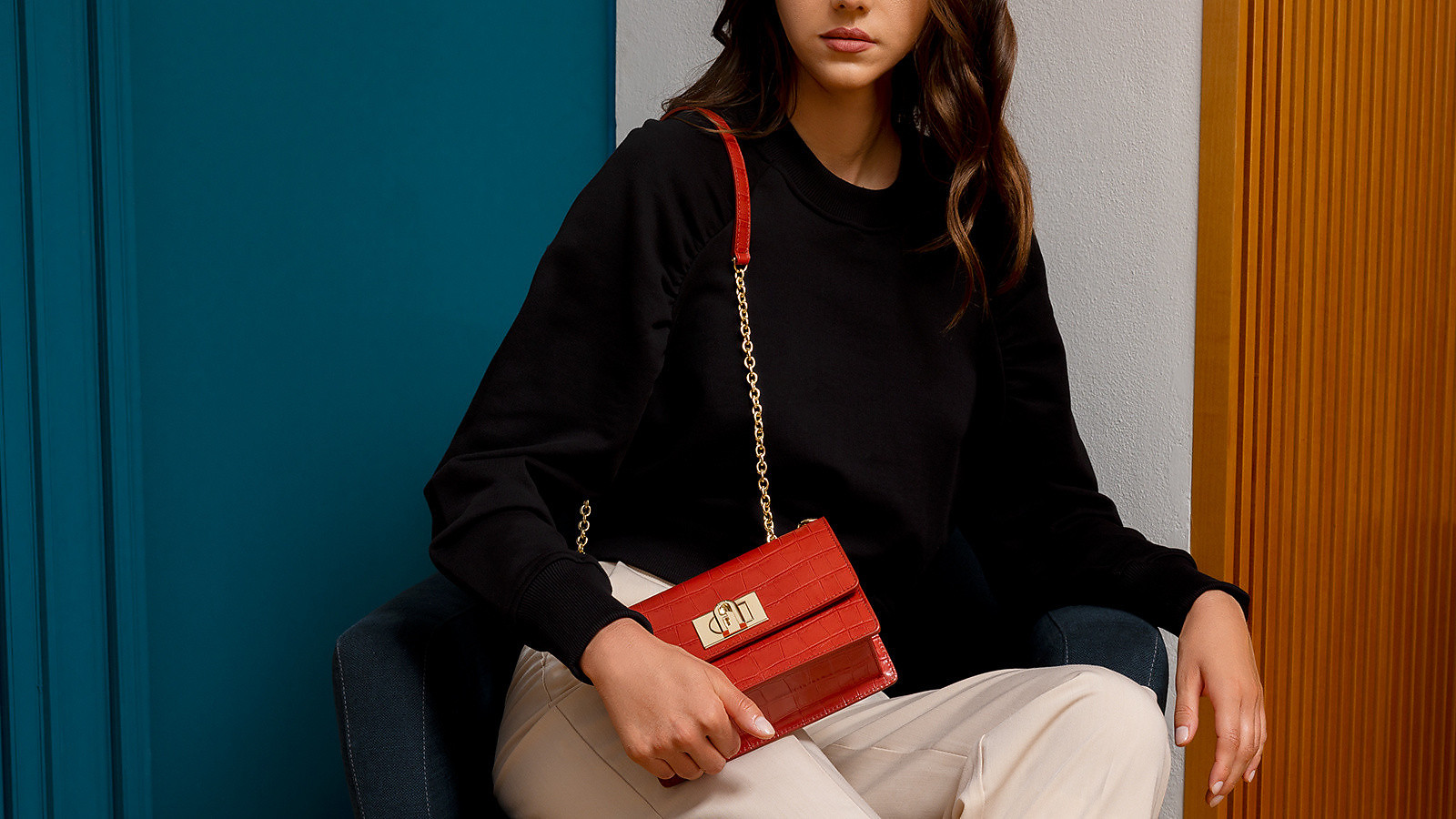 A white girl wearing beige pant and a black sweater is sitting on an armchair. She is looking in front of her and holding on her shoulder a red Furla 1927. The background is a blue wall and a wooden wall