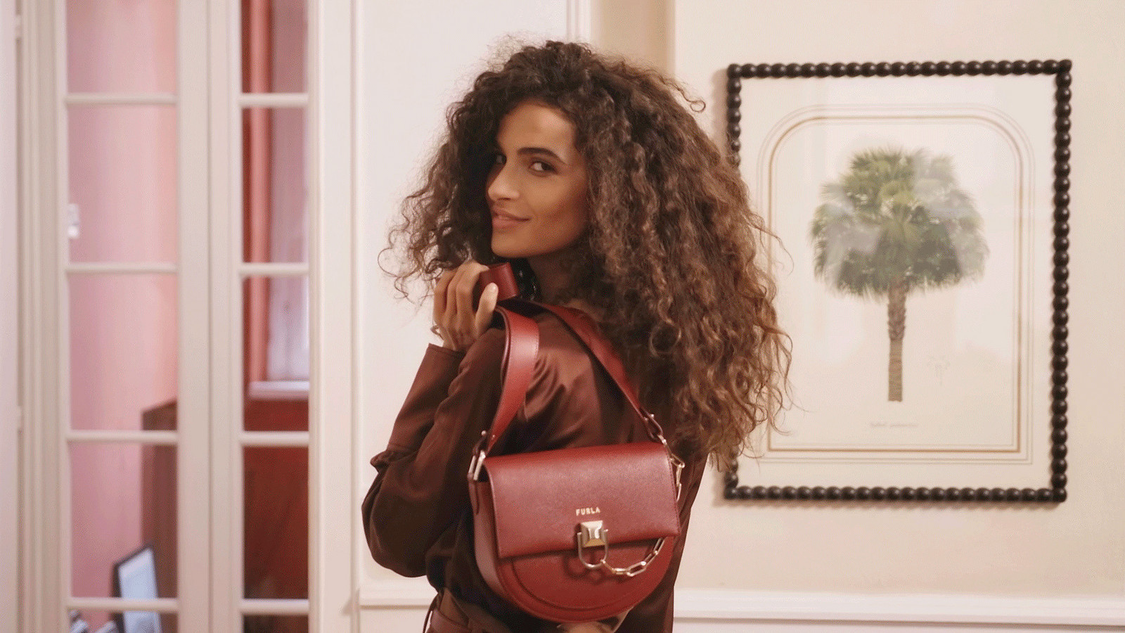 The actress and model Chiara Scelsi is in her Milan apartment, she is holding over the shoulder the new Furla Miss Mimì colorblock.  She's wearing a burgundy sild shirt and smiling at the camera.