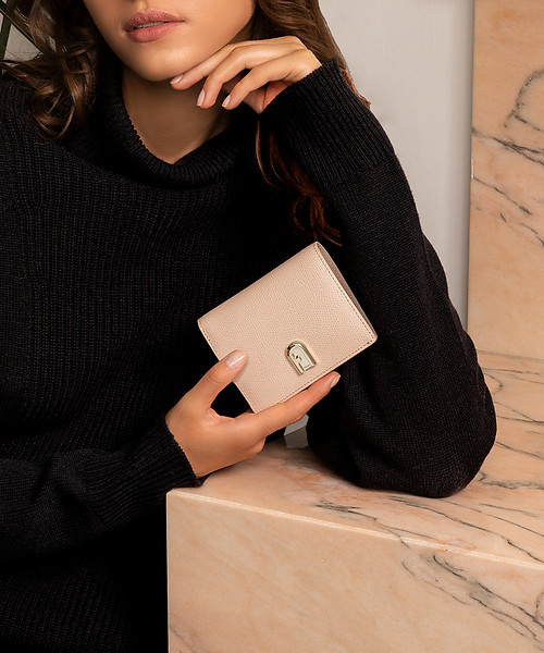 A female model is leaning on a  pink marble table, one hand close to her face, the other  holding the Furla 1927 Sabot wallet.