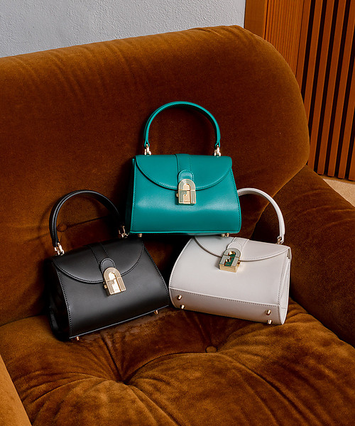 Shot in a Milanese home on a brown velour sofa, three FurlaOpera bags are placed together in colors white, black and emerald.