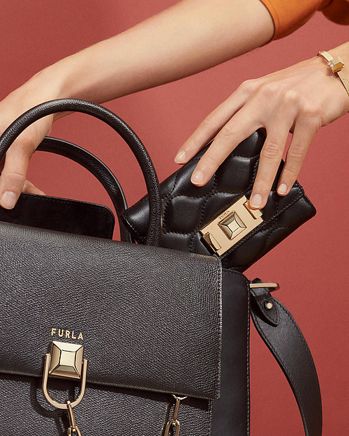 A woman's hand is placing a Furla black wallet inside the new Miss Mimì bag in black. The background is red.